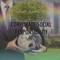 "businessmann holding a small earth sprouting a tree, text says ""corporate social responsibility"" overlaid"